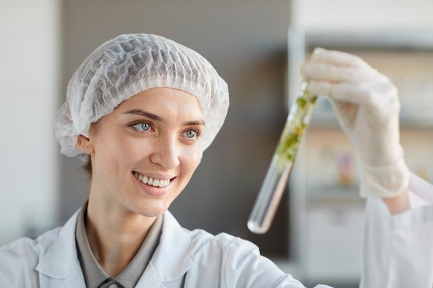 Portret van lachende vrouwelijke wetenschapper reageerbuis met plantmonsters houden tijdens het werken aan onderzoek in biotechnologie lab, kopieer ruimte close-up