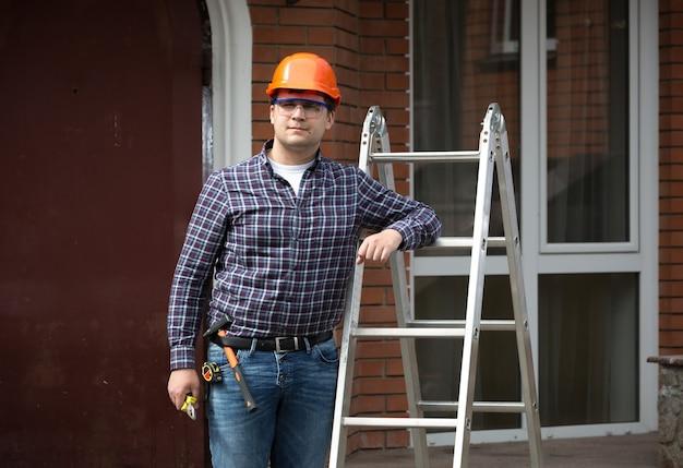 Portret van lachende werknemer in harde hoed leunend tegen metalen ladder