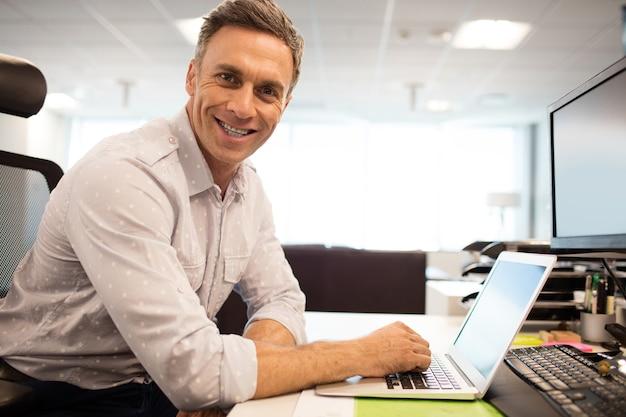 Portret van lachende zakenman met laptop zittend in kantoor