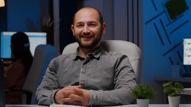 Portret van lachende zakenman zittend aan een bureautafel in het kantoor van een bedrijf