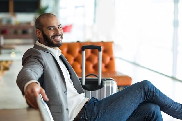 Portret van lachende zakenman zittend op een stoel in wachtruimte