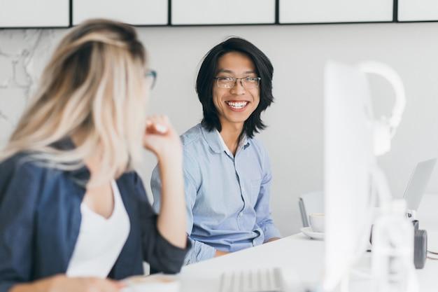 Portret van langharige lachende aziatische man met blonde vrouw. blij chinese kantoormedewerker in blauw shirt een grapje met vrouwelijke collega op de werkplek.