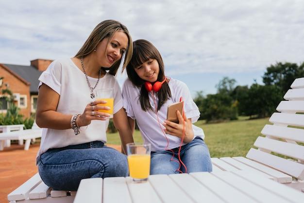 Portret van latina moeder en dochter die van de dag genieten die sinaasappelsap drinken