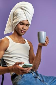 Portret van latino mannelijke chat op telefoon met kopje koffie passen jonge transgender man in witte handdoek