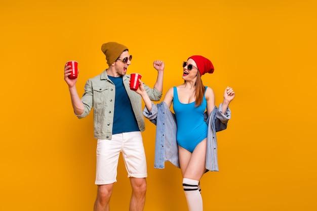 Portret van leuk aantrekkelijk cool modieus blij vrolijk paar buddy collega dansen met plezier bier drinken rust chill geïsoleerd helder levendig glans levendige gele kleur achtergrond