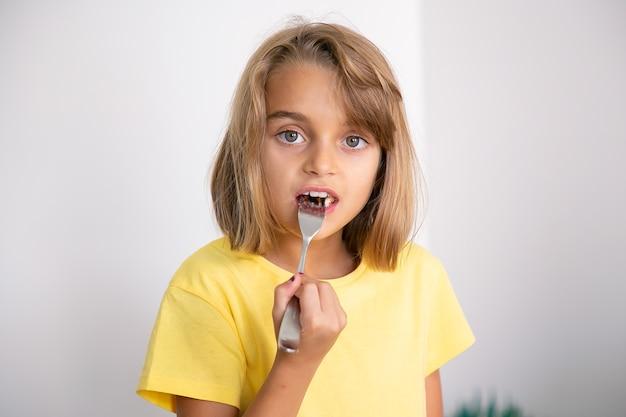 Portret van leuk blondemeisje die cake met vork eten. vrij kaukasisch kind staan, eten. jeugd, feest en vakantie concept