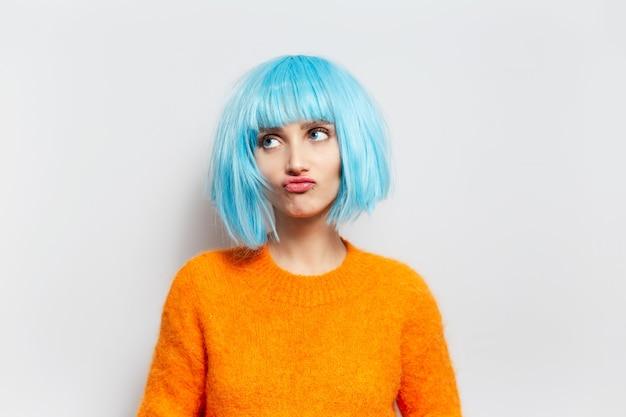 Portret van leuk meisje met blauw haar die in oranje sweater tegen witte muur omhoog kijken.