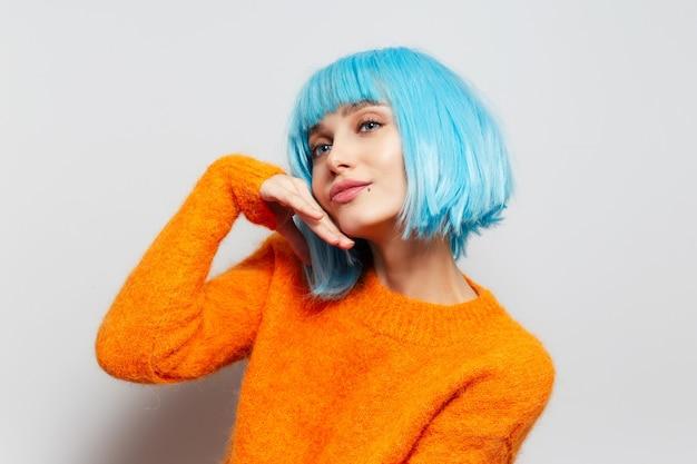 Portret van leuk meisje met blauw haar in oranje sweater op witte muur.