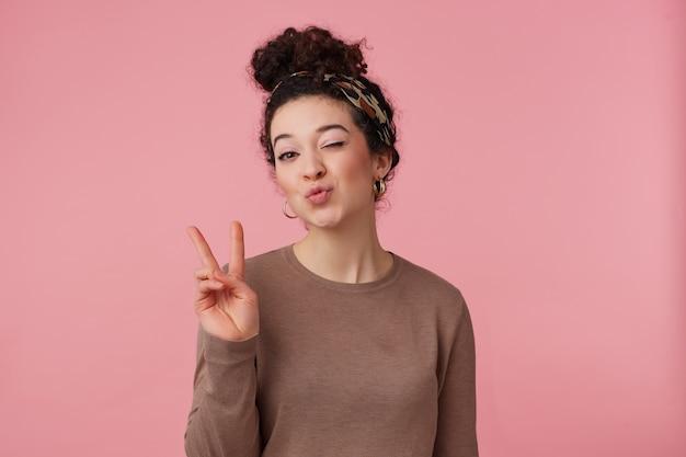 Portret van leuk meisje met donker krullend haarbroodje. hoofdband dragen, oorbellen, bruine trui. heeft make-up. vredesteken laten zien, een kus sturen