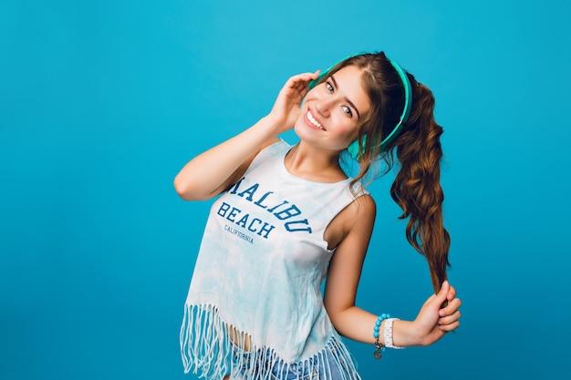Portret van leuk meisje met lang krullend haar in staart op blauwe achtergrond. ze draagt een wit t-shirt, korte broek en luistert naar muziek met een blauwe koptelefoon.