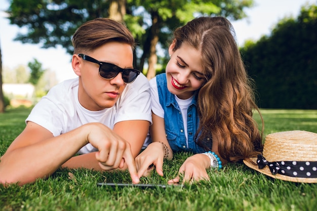 Portret van leuk paar liggend op gras in zomer park. meisje met lang krullend haar, rode lippen lacht naar tablet op gras. knappe jongen in wit t-shirt toont op het scherm.