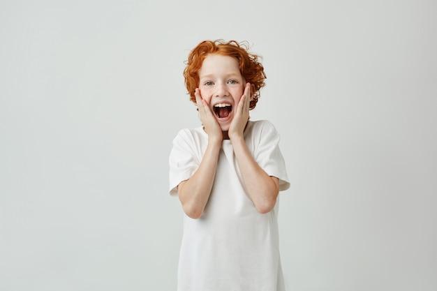 Portret van leuk roodharig kind dat met gelukkige uitdrukking gilt