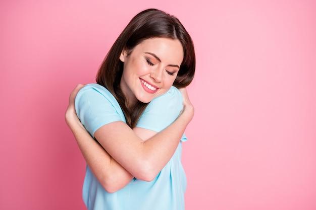 Portret van leuk schattig mooi meisje geniet van comfortabele zelfknuffels geïsoleerd over pastelkleurige achtergrond