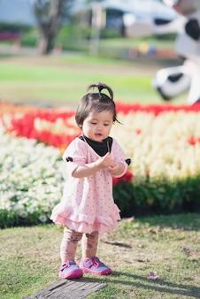 Portret van leuke babyreis bij bloementuin