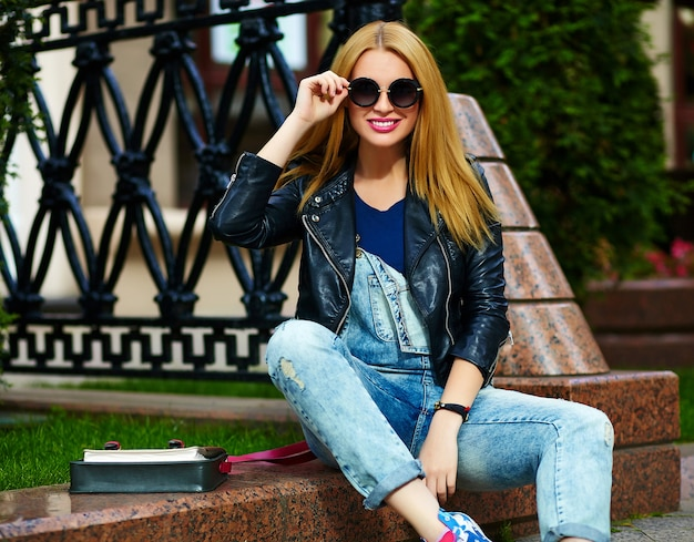 Portret van leuke grappige moderne sexy stedelijke jonge stijlvolle lachende vrouw meisje model in heldere moderne doek buiten zitten in het park in jeans op een bankje in glazen