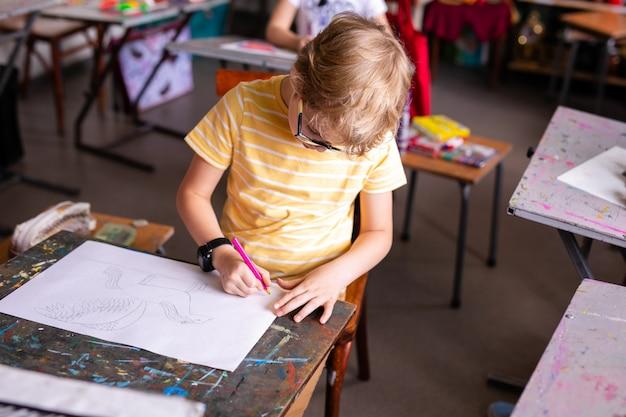 Portret van leuke jongen met schetspen en document bij bureau in klaslokaal