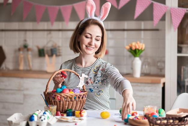 Portret van leuke moeder die een mand met eieren voorbereidt