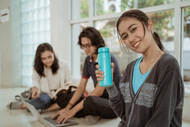 Portret van leuke studenten die flessenwater tonen, zitten in groepen op de grond te werken