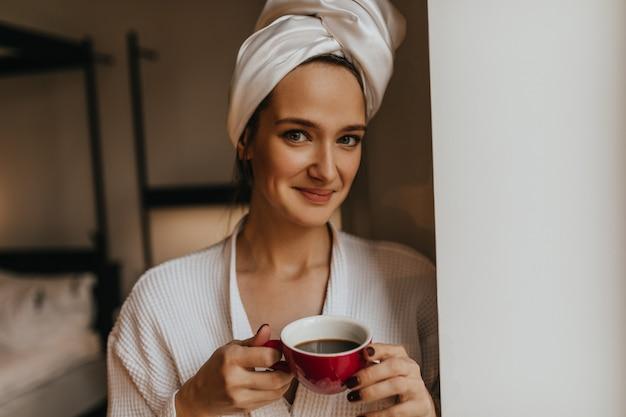 Portret van leuke vrouw met moedervlek op haar gezicht, poseren in badjas en handdoek met kopje koffie in haar handen.