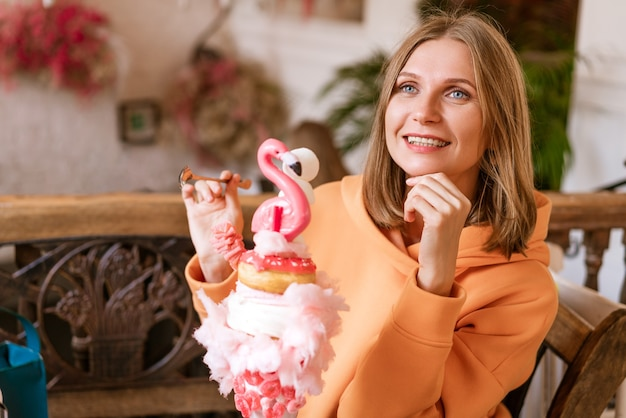 Portret van leuke vrouw zittend aan een tafel in een café met een grote roze taart