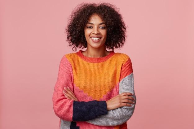Portret van levendig charismatisch aantrekkelijk afrikaans amerikaans meisje met afro kapsel kijkt met opwinding, plezierige glimlach, staan met gekruiste armen, kleurrijke trui dragen, geïsoleerd op roze muur