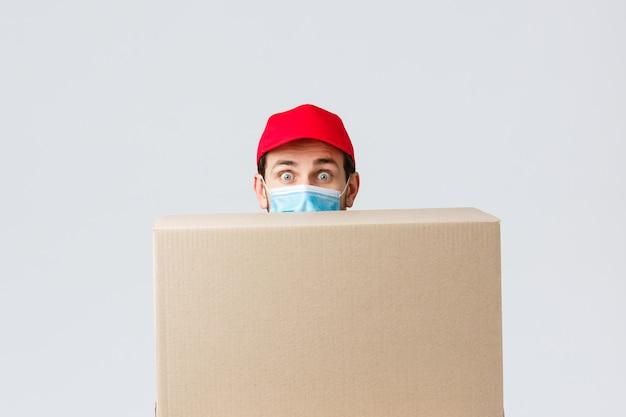 Portret van levering man met gezichtsmasker en doos