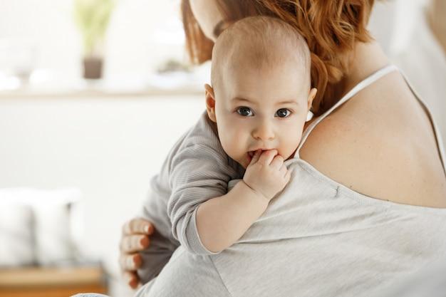 Portret van lief klein kind met grote grijze ogen en hand in mond zetten op moederschouder. moeder knuffel haar kind met liefde. familie concept.