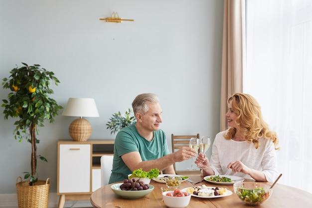 Portret van liefdevolle ouder paar champagne glas verhogen en roosteren terwijl u geniet van een romantisch diner thuis, kopie ruimte