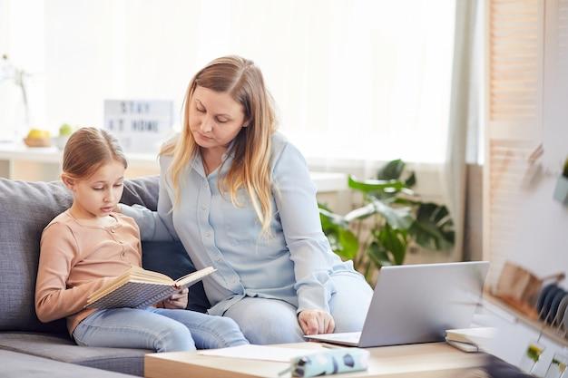 Portret van liefdevolle volwassen moeder kijken schattig meisje boek lezen of studeren zittend op de bank in gezellig interieur, kopie ruimte