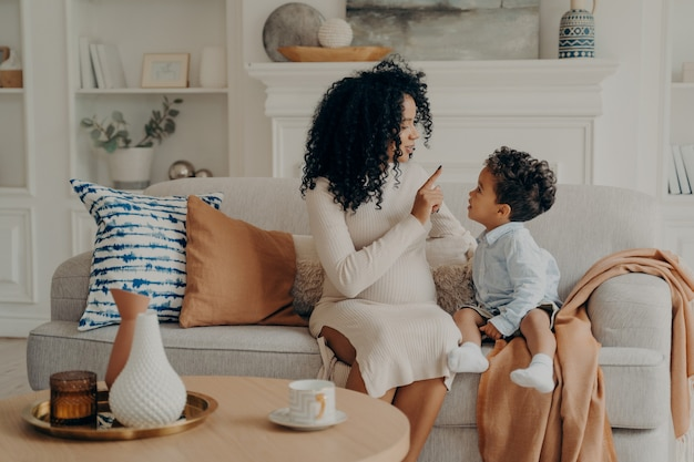 Portret van liefhebbende afro-amerikaanse zwangere moeder die zoontje uitlegt over haar zwangerschap
