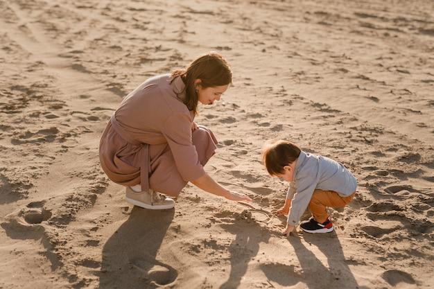Portret van liefhebbende moeder en zijn één jaar oude zoon lopen en spelen met zand.