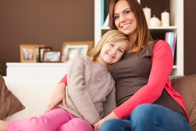 Portret van liefhebbende moeder met dochter op de bank