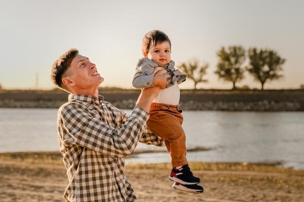 Portret van liefhebbende vader en zijn eenjarige zoon die buiten loopt en speelt.