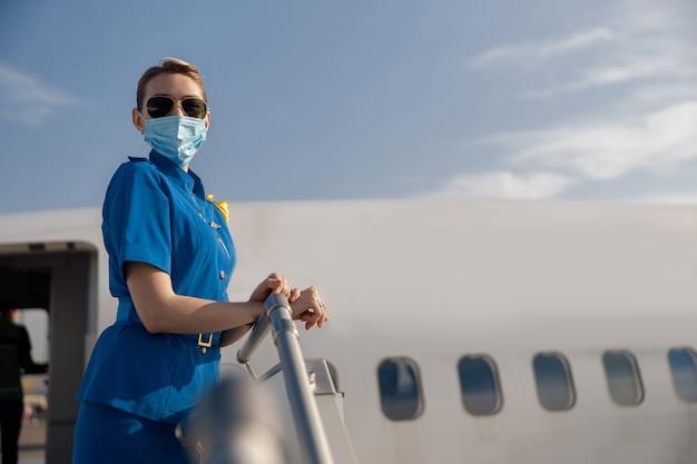 Portret van luchtstewardess in blauw uniform, zonnebril en beschermende gezichtsmaskers die naar de camera kijken, staande op de airstair op een dag. vliegtuigbemanning, bezetting, covid19-concept