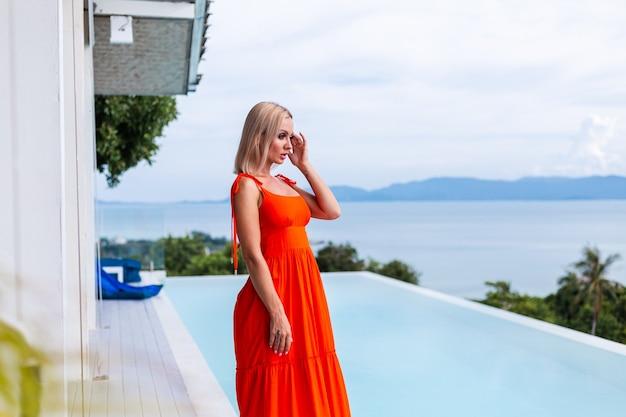Portret van luxe uitziende vrouw in rood oranje avondjurk in rijk hotel Gratis Foto