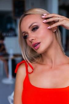 Portret van luxe uitziende vrouw in rood oranje avondjurk in rijk hotel