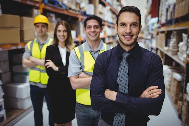 Portret van magazijnbeheerder en werknemers in magazijn