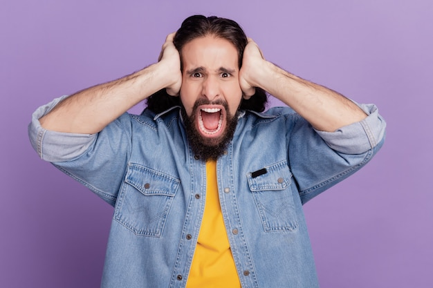 Portret van man bedek oren op paarse achtergrond schreeuw schreeuw geïrriteerde stemming