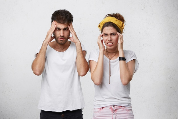 Portret van man en vrouw die geconcentreerde en verbaasde blikken hebben terwijl ze proberen zich iets te herinneren dat hun handen op tempels vasthoudt