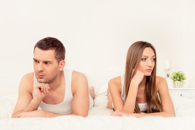 Portret van man en vrouw die ongelukkig in bed liggen