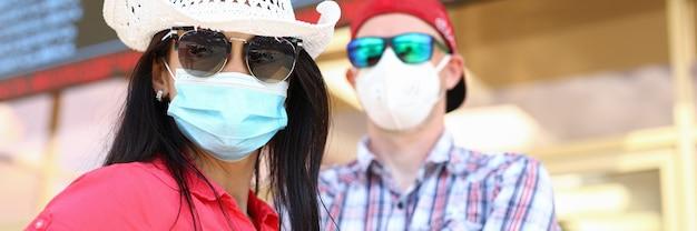 Portret van man en vrouw met medisch beschermend masker onder een informatiebord op de luchthaven