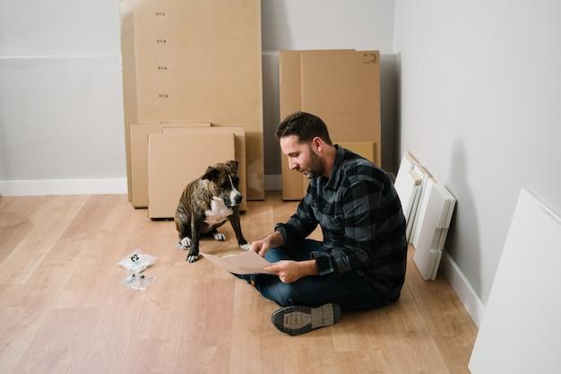 Portret van man en zijn hond die meubels monteren. doe het zelf meubelmontage.