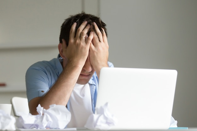Portret van man in de buurt van de laptop, zijn handen sluiten zijn gezicht