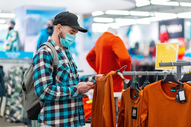 Portret van man in een medisch masker kiest kleding in een winkel