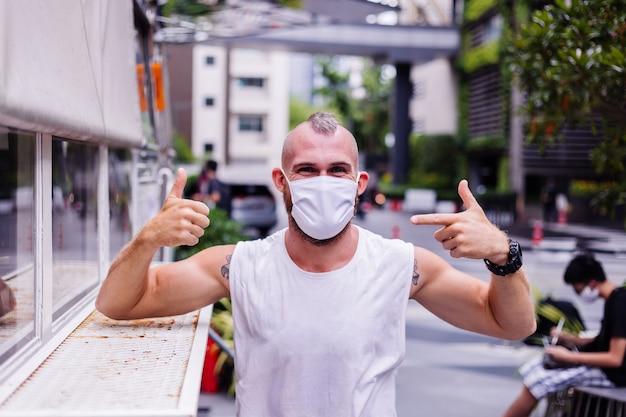 Portret van man in wit medisch masker op het centrale plein in de stad zit op stoel in van café