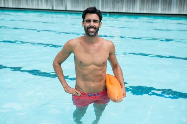 Portret van man in zwembad met reddingsboei