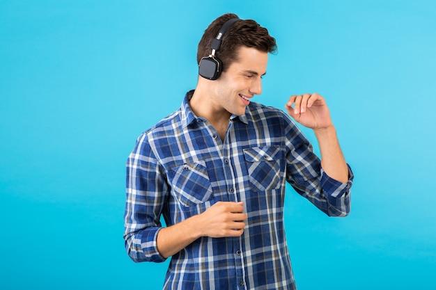 Portret van man luisteren naar muziek op draadloze koptelefoon met plezier op blauw