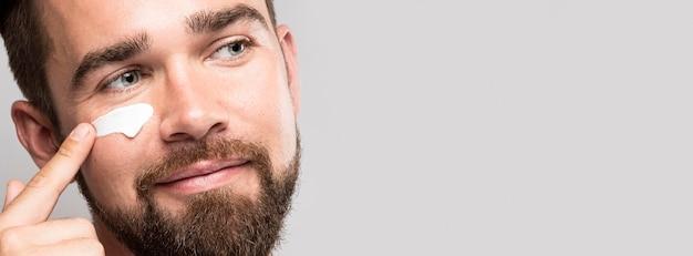 Portret van man met behulp van gezichtscrème met kopie ruimte