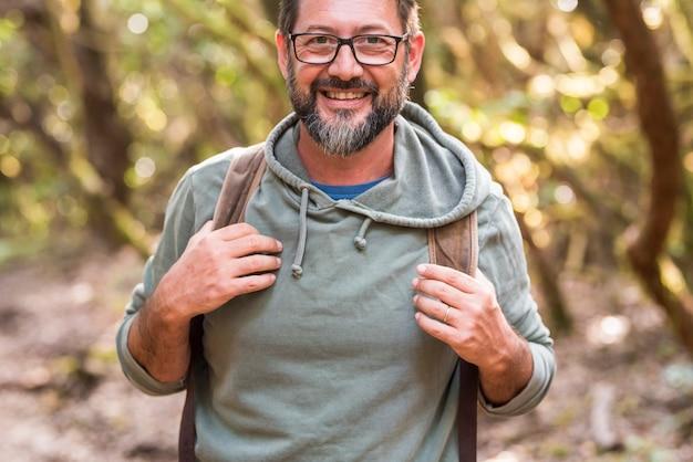 Portret van man met bril en rugzak genieten van het buitenleven