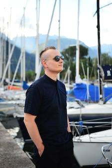Portret van man met elegante zwarte shirt en zonnebril, staande in de buurt van het meer in de alpen